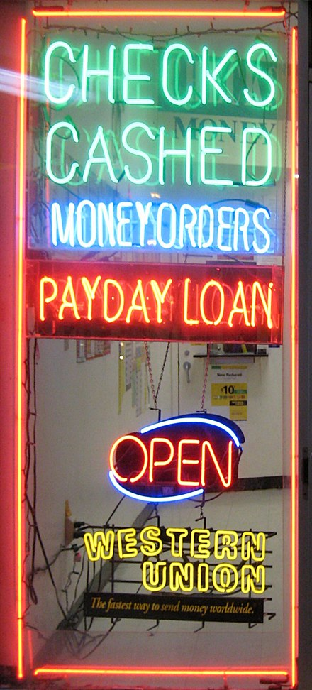 Payday loan businesses lend money to customers, who then owe a debt to the payday loan company. Payday loan shop window.jpg