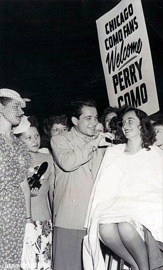 Perry Como - Arriving in Chicago for performances in 1947, Como is met by his young fans, who get a hair trim along with a song.