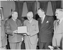 Photograph of President Truman in the Oval Office receiving a sheet of the new Freedom Stamps, issued in honor of the... - NARA - 200200.jpg