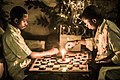 Playing africa's well known drafts game within a candle light in tanzania.jpg