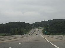 Downhill view of a four-lane divided freeway; the opposing lanes of traffic are separated by concrete barriers.