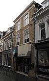 foto van Huis met witgeschilderde lijstgevel en overblijfselen van jaarankers