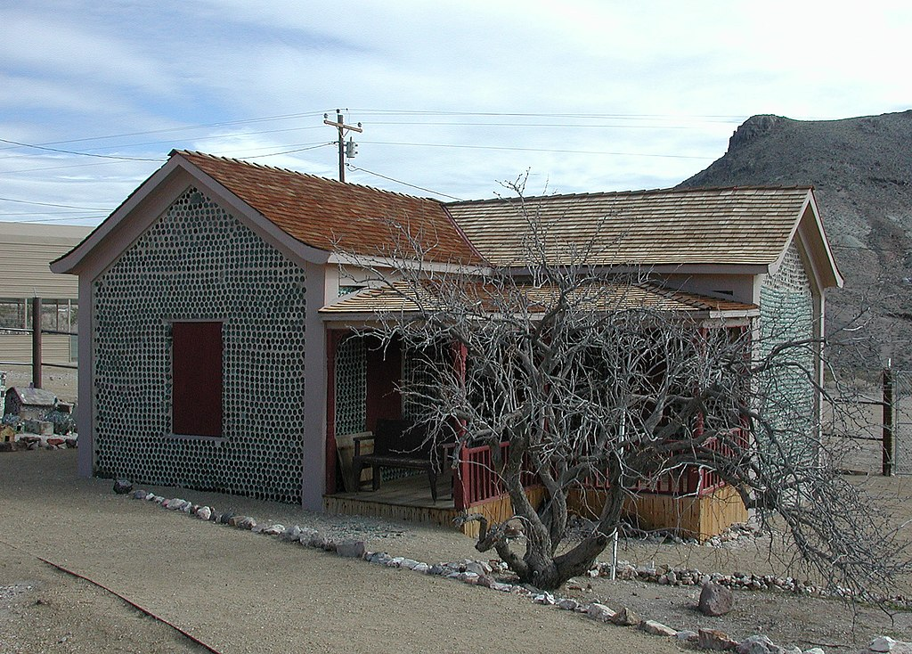 A one-story house with a relatively new roof sits on a manicured bed of gravel. The house and its tidy porch are at least partly made of wood, but the outer walls appear to consist of hundreds of round objects embedded in a masonry matrix. A short, leafless, gnarled tree grows in front of the house along a tidy gravel sidewalk. A barren hill rises in the middle distance.