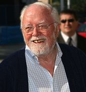 A photograph of a smiling old man with white hair and beard