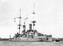 A large light gray warship sits motionless in harbor; it has two tall smoke stacks, both painted with three dark bands for identification.