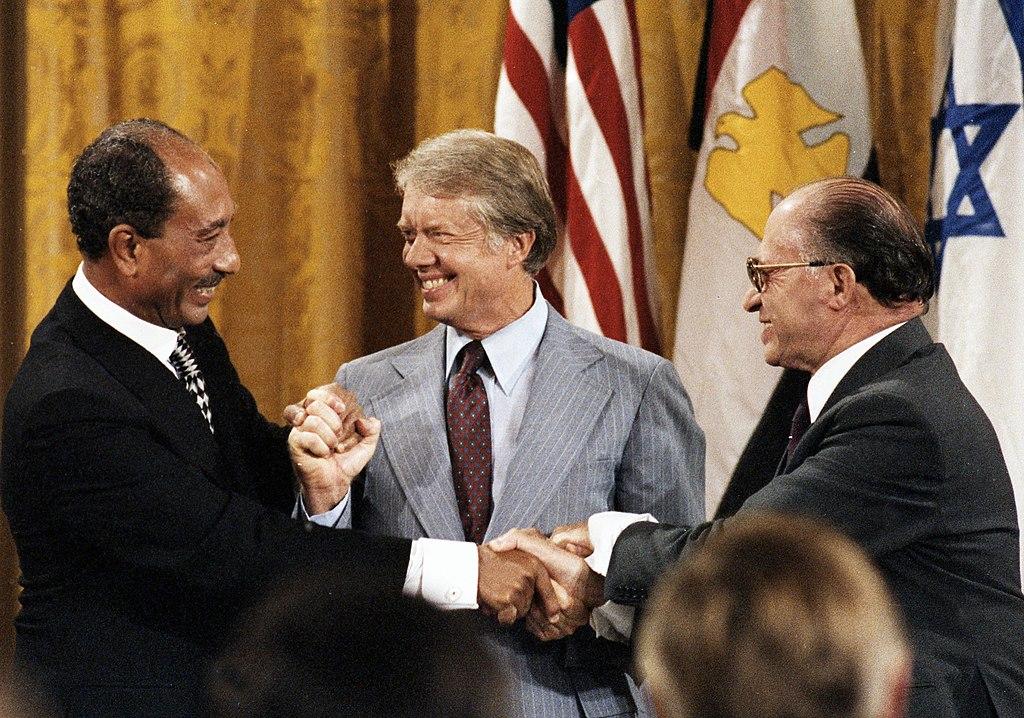 Jimmy Carter, Egyptian President Anwar Sadat, and Israeli Prime Minister Menachem Begin share a triple handshake at the Camp David Accords, 1978 [1024 x 718]