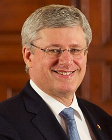 Photograph of Harper in 2014 wearing a dark suit, light blue tie, and a Canadian flag lapel pin.
