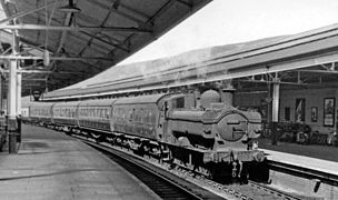 A pannier tank locomotive pulling five passenger coaches through a station