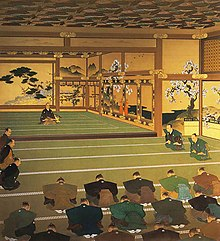 A man seated on a raised floor in front of a group of men who are sitting on a lower floor and bowing slightly. The walls are decorated with paintings of trees.