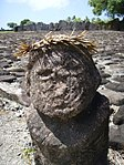 Weathered grey stone bust with a palm frond crown. Grey rocks with white and in between them in the background.