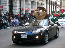 A black open-top sports car with lights on is being driven down an asphalt road. A large furry toy costume, slightly larger than a human is standing in the back seat. It has cream coloured mouth and chest, and dark brown arms and forehead, large whiskers, a grin, large white eyes and two canines. Behind him are some men walking in green costumes. On the left is a crowd watching the parade from the footpath, in front of tall buildings with stone arches.