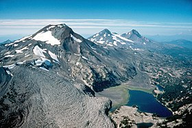 Aerial view from the southeast looking north of the Three Sisters volcanoes, three mountains sparsely covered with ice and snow. From left to right the image shows South Sister, Middle Sister, and North Sister, with a black lava flow in the left foreground.