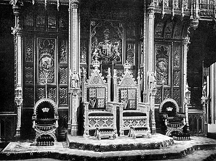 The royal thrones, c. 1902. Note that the Sovereign's throne (on left) is raised slightly higher than the consort's. Thrones in the House of Lords c1902.jpg