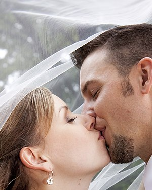 Wedding photograph - a couple kissing under th...