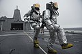 U.S. Navy Damage Controlman 3rd Class Carson Seitz and Hull Maintenance Technician 3rd Class Travis Cole approach the scene to simulate rescuing an injured aircrewman during flight deck drills aboard 130510-N-DR144-189.jpg