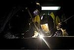 U.S. Navy Hull Maintenance Technician 2nd Class Neil Hopkins, right, and Hull Maintenance Technician 3rd Class Kobi Thurman fabricate an arresting gear cover aboard the aircraft carrier USS Nimitz (CVN 68) 130818-N-JC752-712.jpg