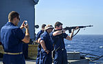 U.S. Navy Lt. j.g. Jason Kressen, left, takes photographs of Gunner's Mate 2nd Class Nicholas Choate as he fires an M14 rifle during a small-arms qualification June 10, 2013, aboard the guided missile cruiser 130610-N-QL471-898.jpg