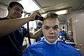 U.S. Navy Ship's Serviceman Seaman Richard Berrios, left, cuts the hair of Hull Maintenance Technician 3rd Class Ivan Knighten in the barbershop aboard the amphibious dock landing ship USS Pearl Harbor (LSD 52) 130523-N-WD757-060.jpg
