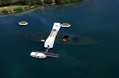 An aerial view of the USS Arizona Memorial at Pearl Harbor in 2002. During the attack on Pearl Harbor on December 7, 1941, a bomb from a Japanese Nakajima B5N struck Arizona between the first and second gun turrets, causing a catastrophic explosion that sunk the ship, where she remains today, with 1,102 of her crew still entombed inside.