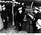 Lt. Eric Purdon, the ship's first commanding officer, reads the official orders directing him to assume command.