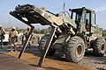 US Navy 041116-M-1250B-013 A Seabee assigned to Naval Mobile Construction Battalion Four (NMCB-4), Kalsu Detachment, operates a fork life as it pushes large pieces of sheet metal over an impact crater.jpg