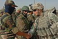 US Navy 060830-N-4097B-014 U.S. Army Lt. Alan Boyes, right, with Charlie Company, 1st Battalion, 68th Armored Regiment, 4th Infantry Division, shakes the hand of an Iraqi army soldier.jpg