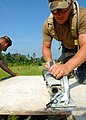US Navy 070613-N-0553R-003 Builder 1st Class Bill Waldron, of Naval Mobile Construction Battalion (NMCB) 1, cuts plywood planks during construction of a battalion aid station.jpg