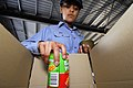 US Navy 070705-N-4614W-075 Operations Specialist 2nd Class Mayra Ruiz, assigned to the multi-purpose amphibious assault ship USS Essex (LHD 2), loads a charity box at Food Bank Townsville.jpg