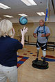US Navy 071015-N-5086M-002 U.S. Army Spc. Saul Martinez trains with the medicine ball while standing on a balancing tool and using the hands-free harness walking gait-training device during a therapy session.jpg