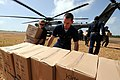 US Navy 080814-N-8907D-046 Operations Specialist Seaman Apprentice Richard Vickers and Electronics Technician 2nd Joshua Seabourn, both embarked aboard the amphibious assault ship USS Kearsarge (LHD 3), unload boxes of food don.jpg