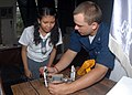 US Navy 091015-N-6692A-049 Electronics Technician 3rd Class Zachary Sievers, from Nekoosa, Wis. assigned to the dock landing ship USS Tortuga (LSD 46), explains how a voltage regulator works to Jomarie Briones.jpg