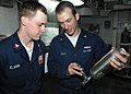 US Navy 091021-N-6688C-067 Machinist's Mate 2nd Class Joseph Gray instructs Machinist's Mate 2nd Class Chris Klamm on what to look for while inspecting a liquid oxygen sample cylinder.jpg
