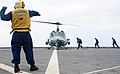 US Navy 091030-N-6692A-061 Boatswain's Mate 2nd Class Carlos Gonzales signals the pilot while Sailors approach to secure a Marine Corps UH-1N Huey helicopter aboard the amphibious dock landing ship USS Tortuga (LSD 46).jpg