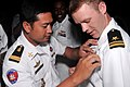 US Navy 100215-N-8335D-388 Lt. Tim Monipisey, left, a Sailor with the Royal Cambodian navy, exchanges warfare pins with Lt. j.g. Bradley Feige.jpg