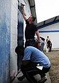 US Navy 110604-N-QD416-122 Cmdr. Ray Houk, from Shelby, Ohio, and Colombian citizens paint the walls of the Institucion Ciudadela Educativa Tumaco.jpg