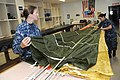 US Navy 110715-N-VE260-043 Aircrew Survival Equipmentman 3rd Class Christina Cataldo, left, pulls the slack on a parachute while Aircrew Survival E.jpg