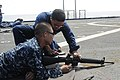 US Navy 110824-N-WV964-015 Boatswain's Mate 2nd Class Dennis Castro explains gun safety to Boatswain's Mate Seaman Guozhi Lei before a live-fire ex.jpg