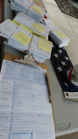 an English-language New York State voter registration form on a clipboard with a pen, near stacks of Spanish, Chinese, Korean, and Bengali language voter registration forms, on a table near a US flag; By Sumanah [CC BY-SA 4.0 (https://creativecommons.org/licenses/by-sa/4.0 )], from Wikimedia Commons