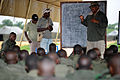 Wahid Ali, company trainer for Congolese soldiers assigned to the Congolese Light Infantry Battalion, reviews basic military principles of entering and clearing a building at Camp Base in Kisangani, Congo, May 100505-F-FW561-057.jpg