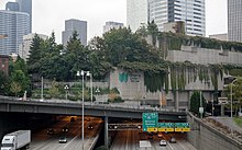 A concrete building with trees and plants hanging from its roof. The building sits on a bridge over a wide freeway, with cars and trucks streaming by.