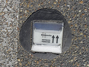Raised pavement marker - A white retroreflective raised pavement marker (Stimsonite design)