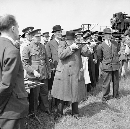 Churchill takes aim with a Sten submachine gun in June 1941. The man in the pin-striped suit and fedora to the right is his bodyguard, Walter H. Thompson. Winston Churchill As Prime Minister 1940-45 H10688.jpg