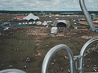 From a place up high and distant is viewed a vast open field of grass, trodden bare and brown in places with little people dotted around like ants beside enormous tents, marquees, performance stages hosting deafening arrays of musical-event speakers. The horizon is low and far away and the sky is dotted with broken clouds.