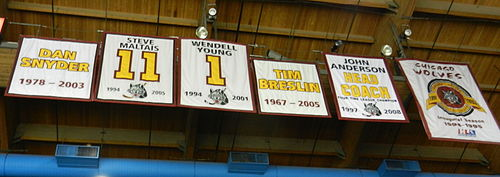 six banners hanging from the ceiling. They vary in size and shape each has yellow lettering with maroon trim describing what they represent.