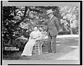 Woodrow Wilson, full-length portrait, standing next to his wife, Ellen, seated in a chair LCCN96520621.jpg