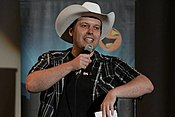 Man in cowboy hat holding microphone and leaning on microphone stand.