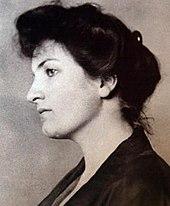 Kop en schouders fotoportret van een aantrekkelijke donkerharige jonge vrouw die naar links kijkt met een bedachtzame uitdrukking