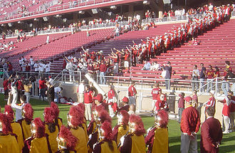 Stanford Band - The LSJUMB (background) doing the Roman salute, some holding dollar bills, as USC's fight song is played by the Spirit of Troy in the (foreground).