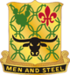 """A Gold color metal and enamel device 11⁄8 inches (2.9cm) in height overall consisting of a shield blazoned: Or, chain mail Vert, in chief a prickly pear cactus of the last and a fleur-de-lis Gules and in base a carabao affronté Sable. Attached below and to the sides of the shield a Black scroll turned Gold inscribed """"MEN AND STEEL"""" in Gold letters."""