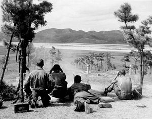 A machine gun firing at a river with four soldiers watching